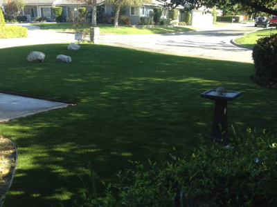 Artificial lawn in a front yard with a bird bath