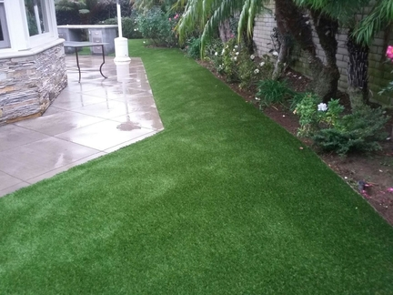 Artificial grass boarder between a walkway and a planter with a block wall, Whittier CA