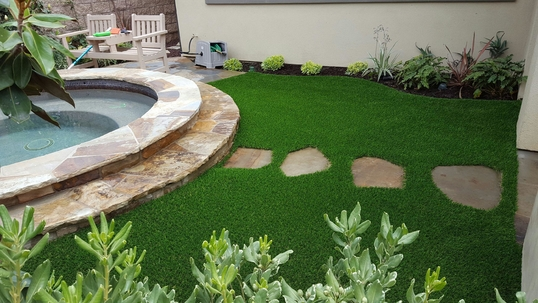 Artificial grass surrounding a Jacuzzi and stepping stones
