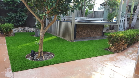 Synthetic lawn installed around a raised Jacuzzi and walking path