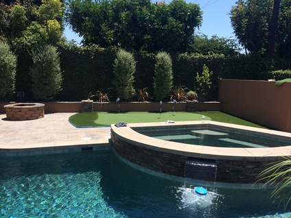 A pool and raised Jacuzzi with a synthetic putting green in the corner of the yard, Whittier CA