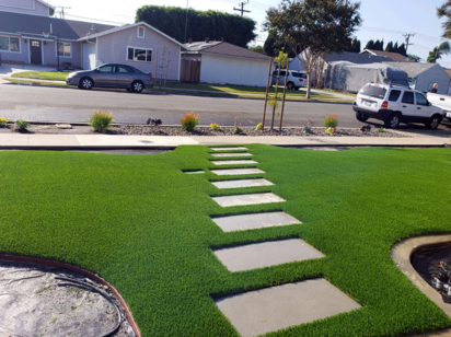 Artificial grass installed in a front yard with square stepping stones from the curb to the house
