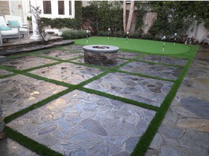 A photo of strips of artificial turf bordering stone squares and a fire pit, Whittier CA