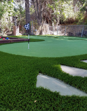 Artificial grass putting green installed in a back yard next to a play area, Whitier CA
