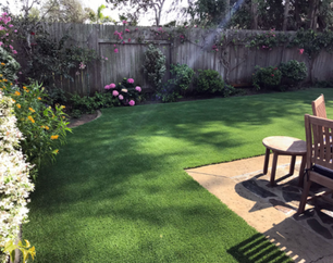 Synthetic grass installed in a back yard with patio furniture and flowering planters