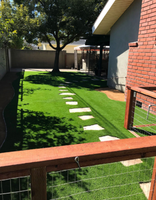 A picture of artificial grass in a back yard with a chicken wire fence and irregular stepping stones, Whittier CA