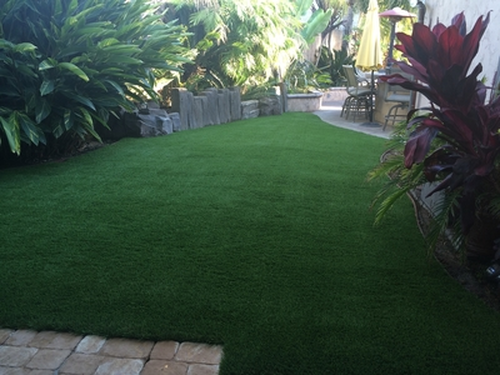 A photo of a lush looking synthetic lawn in a back yard between planters, Whittier CA