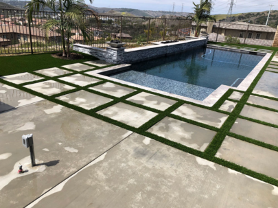 A picture of artificial grass infill around pavings stones surrounding a pool, Whittier CA