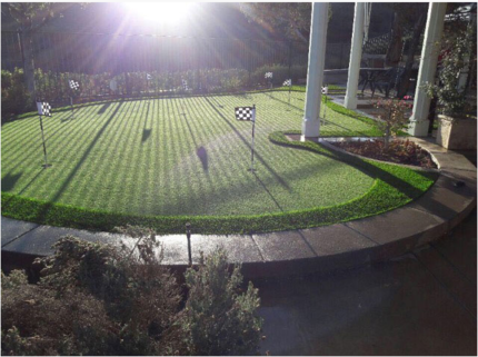Artificial turf putting green lighted up at night next to some white pillars, Whittier CA